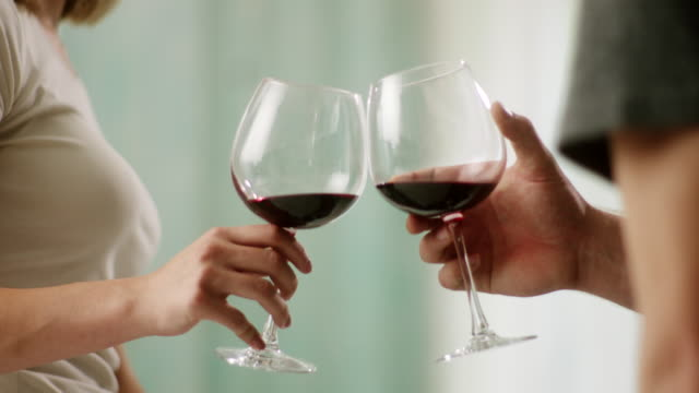 Close-up, man and woman toasting with red wine Close-up, man and woman toasting with red wine glasses red wine stock videos & royalty-free footage