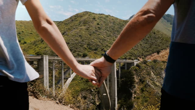 Close-up man and woman walk together holding hands at epic beautiful view of Bixby Creek bridge in Big Sur California. video