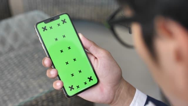 närbild man närbild av att använda smarta telefon, grön skärm - telefonmeddelande bildbanksvideor och videomaterial från bakom kulisserna