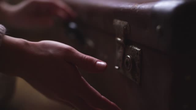 close-up man hands lower vintage suitcase to floor and open it in slow motion - scatola del tesoro video stock e b–roll