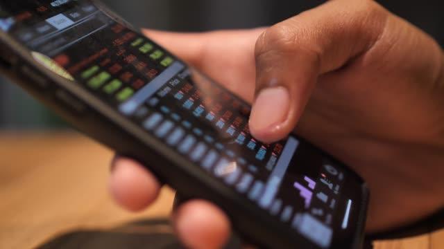 close-up man looking at graph market data on smart phone - azioni e partecipazioni video stock e b–roll