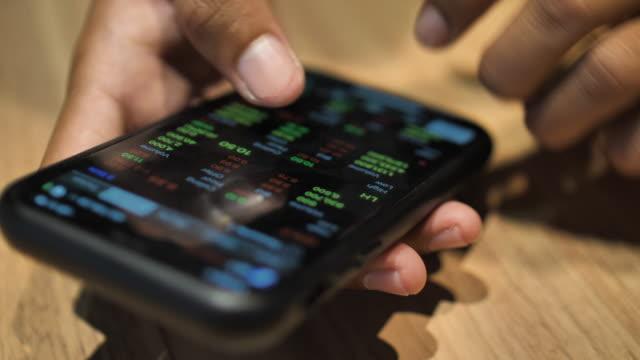特寫人物在智慧手機上查看股市資料 - 區塊鏈 個影片檔及 b 捲影像