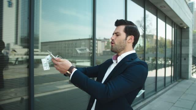 closeup mann wirft geld. geschäftsmann feiert sieg mit bargeld - billionär stock-videos und b-roll-filmmaterial