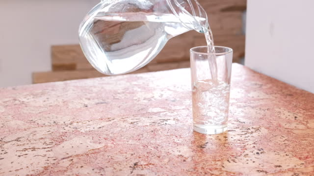 closeup man's hand pouring a water from decanter to glass and takes a glass. - decanter video stock e b–roll