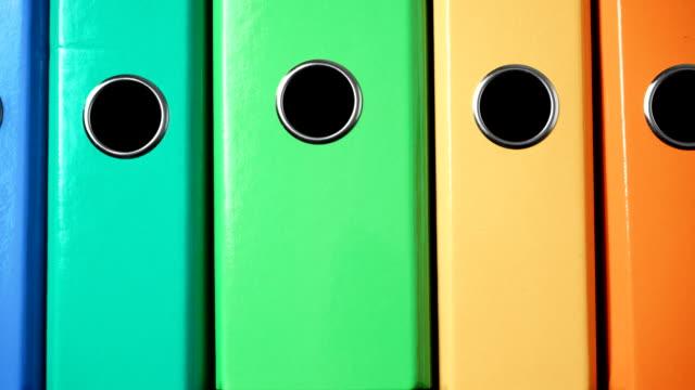 vídeos de stock e filmes b-roll de closeup many colorful binders as office background 4k - dossier