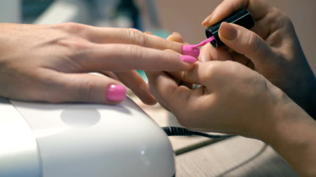 vidéos et rushes de gros plan, maître de manucure: application de laque rose sur ongles sur main de femme - ongle