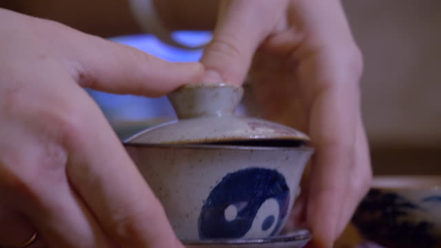 Closeup master pouring infusion tea from gaiwan in fairness bowl at tea ceremony Close up pour out hot tea infusion from gaiwan to fairness pitcher bowl steam rise. Traditional Chinese tea ceremony. Hands tea master preparing tea in yixing clay pottery yin yang sign. Backlight yin yang symbol stock videos & royalty-free footage