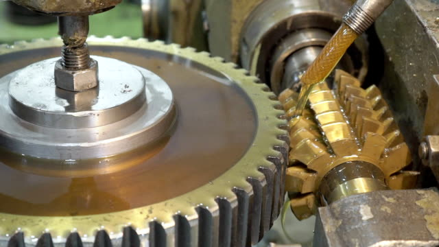Close-up mechanism makes vertical grooves in pinion with oil Close-up mechanism makes vertical grooves in pinion with oil. Jet of cooling yellow liquid polishes parts that are manufactured in a slow process in plant. metalwork stock videos & royalty-free footage