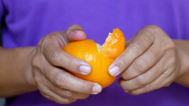 Close-up : Men are peeling orange video