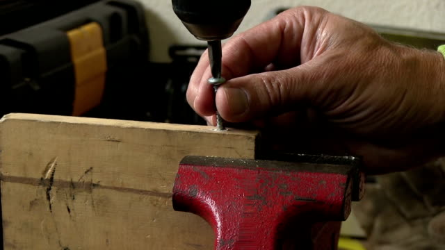 closeup metal screw into wood in red vice with sound video