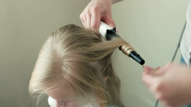Close-up Mom curls hair her little daughter. video
