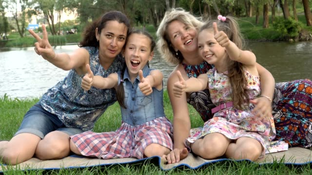 Close-up, mothers with young daughters play and have fun sitting on the lawn in the Park at sunset on a summer day by the river. Family outdoor recreation. The concept of family happiness. 4K.