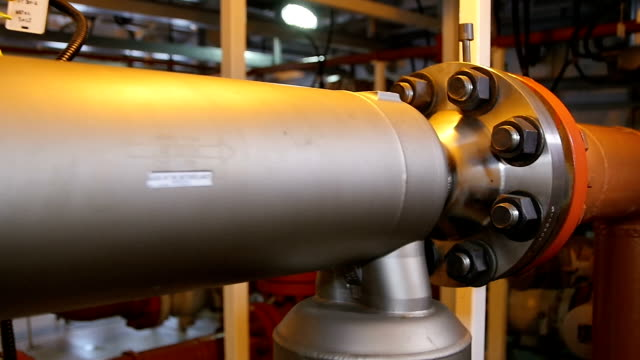 Closeup Motion along Big Metal Gas Pipe at Bright Light Closeup motion along big metal gas pipe fastened with bolts and nuts in brightly lit factory workshop bolt fastener stock videos & royalty-free footage