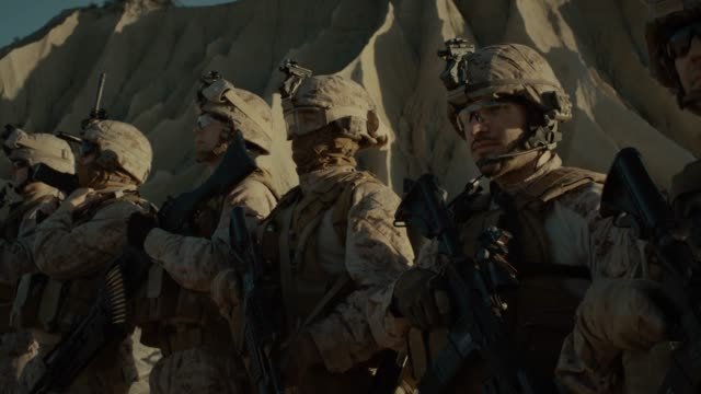 Close-up Moving Shot Group of Fully Equipped Soldiers Standing in a Line in the Desert. Paratroopers Ready for the Mission in Desert Region Close-up Moving Shot Group of Fully Equipped Soldiers Standing in a Line in the Desert. Paratroopers Ready for the Mission in Desert Region. Shot on RED EPIC-W 8K Helium Cinema Camera. veteran stock videos & royalty-free footage