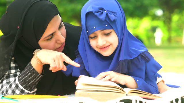 close-up: muslim girl learning on book while laying down with her mother in public park in morning - hijab video stock e b–roll