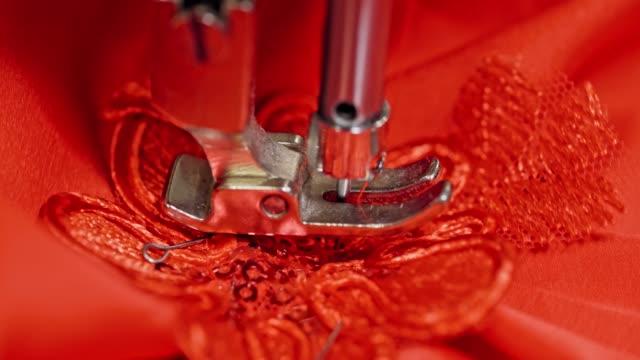 nahwärme einer nähmaschine, die auf rotem stoff arbeitet. - kurzwaren stock-videos und b-roll-filmmaterial
