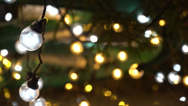 Closeup New Year's bulb of garland on background of bokeh flickering lights. Christmas blurred background. 4K Ultra HD