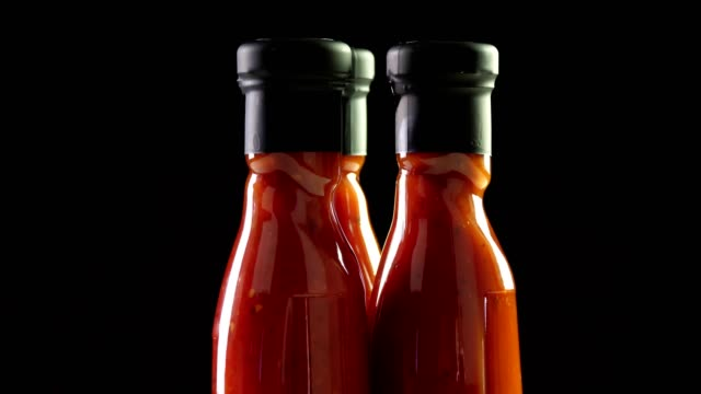 close-up, nicely arranged several small bottles of tomato sauce, food products rotate on black background. grocery online shopping. food delivery