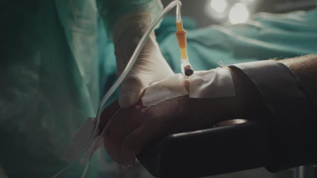 närbild, sjuksköterska som håller patientens hand - skyddshandske bildbanksvideor och videomaterial från bakom kulisserna
