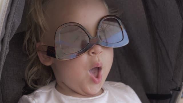 eine nahaufnahme eines baby-mädchen-gesichts, das eine weibliche sonnenbrille auf dem kopf trägt - menschlicher kopf stock-videos und b-roll-filmmaterial