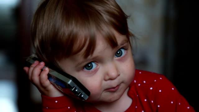 il primo tempo di un bambino parla al telefono - ear talking video stock e b–roll