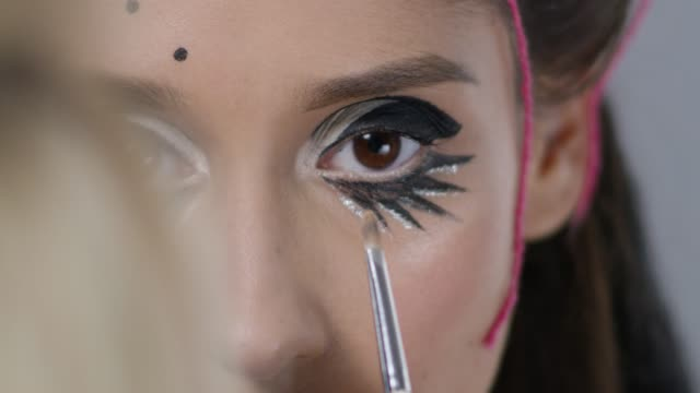 Close-up of a backstage. Make-up artist puts eyeshadows on fashion model`s eyes. Fashion video. video