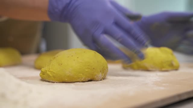 a close-up of a bakers hands rounding and shaping dough into classic bread loafs. professional bakery concept - formare pane video stock e b–roll