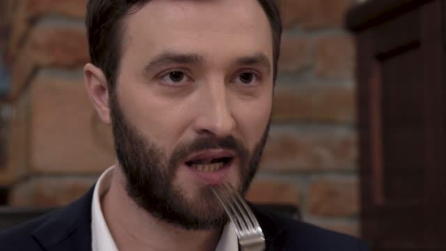 Close do rosto de um homem barbudo colocando um pedaço de comida na boca em um restaurante requintado. - vídeo
