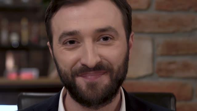 Close do rosto de um homem barbudo limpando a boca com um guardanapo de um restaurante requintado. - vídeo