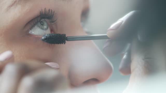 vidéos et rushes de un plan rapproché d'une esthéticienne appliquant le mascara à des cils de modèles - pinceau à maquillage