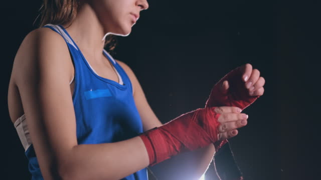 vídeos de stock e filmes b-roll de close-up of a beautiful athletic female boxer pulls red bandages on the hands of a female fighter. steadicam shot - campeão desportivo