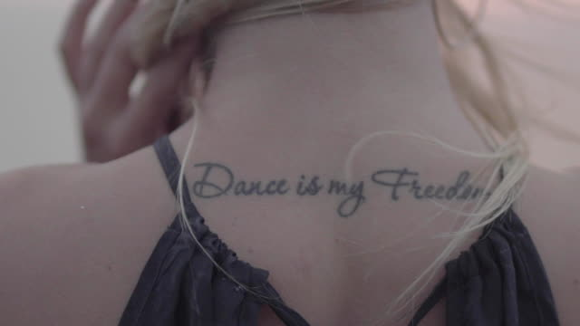 close-up of a beautiful young blonde with tattoo on a back saying dance is my freedom. slow motion 4k. - tatuaggio video stock e b–roll