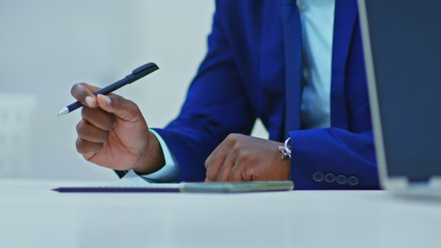 Close-up of a black businessman's hand with a pen, signs papers. Dark-skinned businessman signs a contract. 4k, ProRes