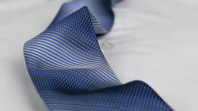 Close-up of a blue tie lying on a white shirt. Dolly shot. Close-up of a blue tie lying on a white shirt. Dolly shot. Fashionable subject video button down shirt stock videos & royalty-free footage