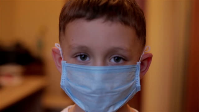 Close-up of a boy wearing a mask at a reception at the doctor video