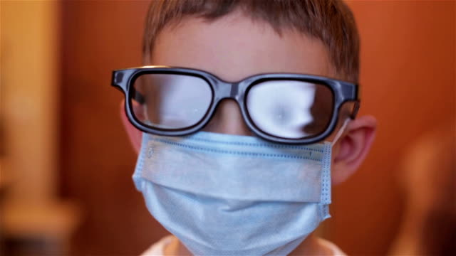 Close-up of a boy with glasses and mask in hospital video