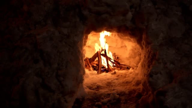 Close-up of a bright bonfire burning inside of an igloo