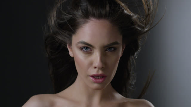 close-up of a brunette fashion model`s face. wind is blowing her hair. fashion video. - seduzione video stock e b–roll