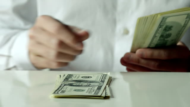 Close-up of a Businessman Lays Out Hundred Dollar Bills on the Table video