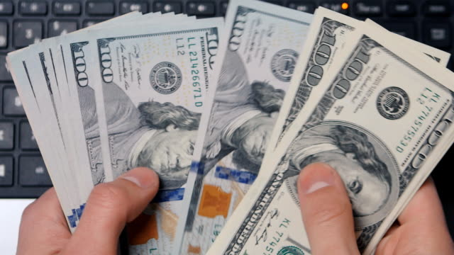 Close-up of a businessman's hand counts money near a laptop. video