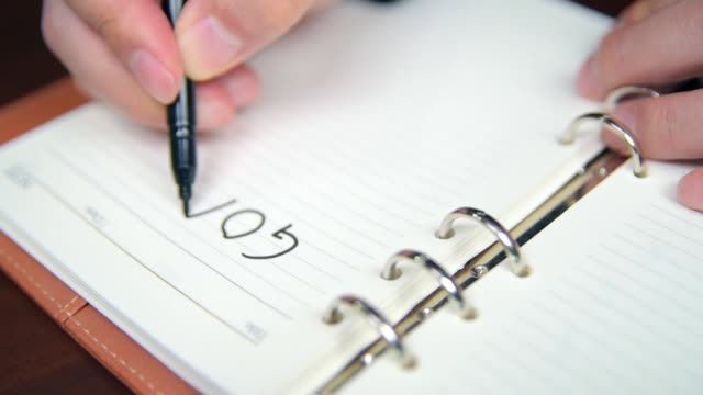 Close-up of a businessman's hand writing goals and list in the diary.