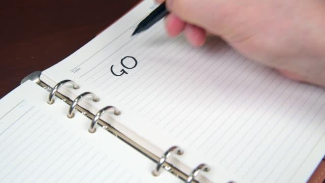 vídeos y material grabado en eventos de stock de primer plano de los objetivos de escritura de mano de un hombre de negocios y la lista en el diario. - objetivo