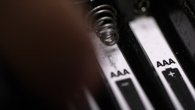Close-Up of a Caucasian Person's Hands Installing Triple A (AAA) Batteries into an Electronic Device Close-Up of a Caucasian Person's Hands Installing Triple A (AAA) Batteries into an Electronic Device positioning stock videos & royalty-free footage