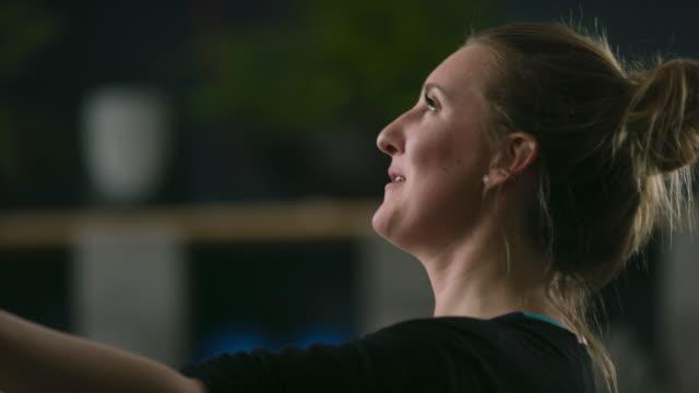 närbild av en kaukasiska kvinnor i tjugoårsåldern leder övningar samtidigt räknar högt för sina elever i gym - gym skratt bildbanksvideor och videomaterial från bakom kulisserna