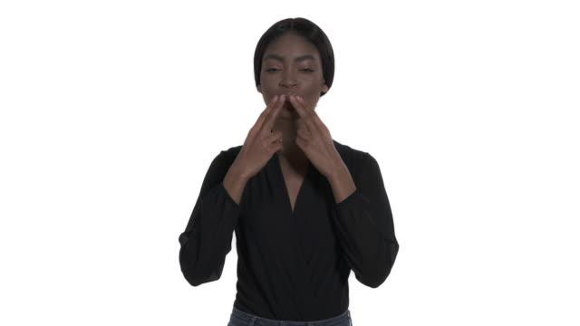 nahaufnahme einer charmanten jungen frau, die lippen faltet und handflächen hält, um luftkuss zu senden. körpersprache. isoliert, auf weißem hintergrund - schwarzes haar stock-videos und b-roll-filmmaterial