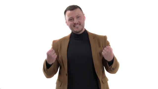 stockvideo's en b-roll-footage met close-up van een vrolijke knappe mens die positieve gebaren uitdrukt. emotie van succes. lichaamstaalconcept - men blazer
