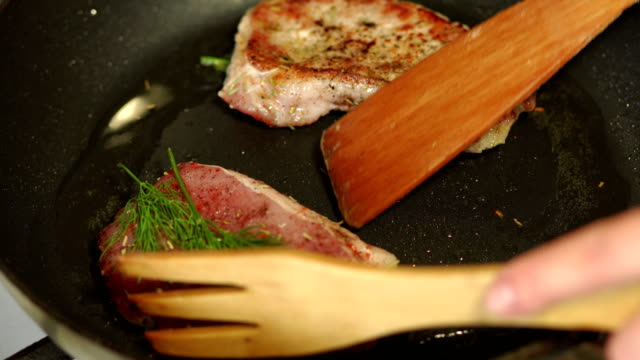 close-up of a chef flips pork chops in a skillet. - filetto video stock e b–roll