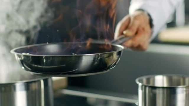 vidéos et rushes de gros plan d'un cuisinier préparation plat style flambé sur un pan. l'huile et l'alcool s'enflammer avec une flamme nue. - haute gastronomie