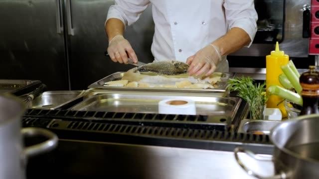 zbliżenie szefa kuchni wyciąga pieczone ryby dorado z soli w kuchni restauracyjnej - karp filmów i materiałów b-roll