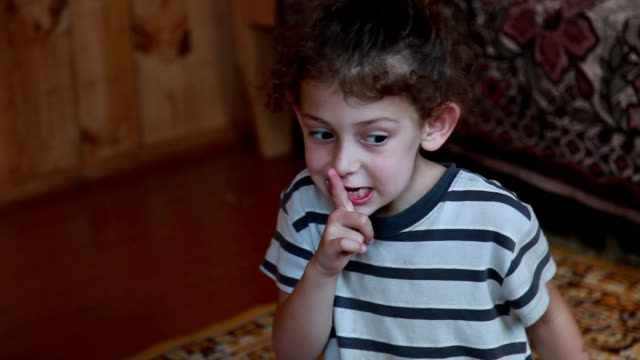close-up of a child putting finger on lips - cisza filmów i materiałów b-roll